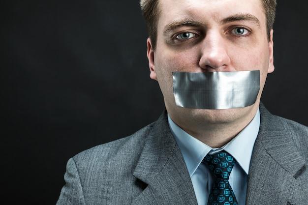 Homem com boca coberta por fita adesiva