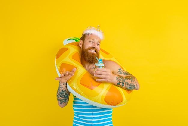 Homem com bóia salva-vidas e coroa de princesa bebe suco de frutas