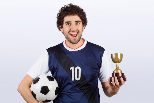 Homem com bola de futebol e troféu.