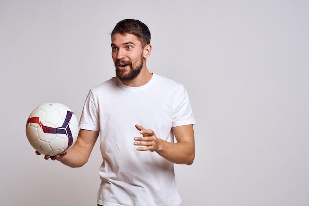 Homem com bola de futebol jogando fundo claro de treino