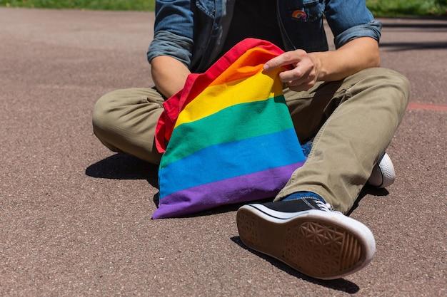 Homem com bolsa reutilizável arco-íris e emblema lgbt mês do orgulho