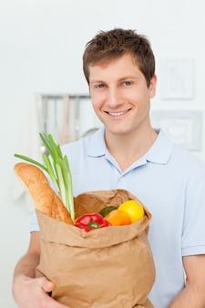 Homem com bolsas de compras na cozinha