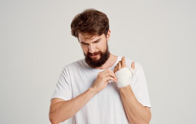 Homem com braço enfaixado traumatologia tratamento problemas de saúde