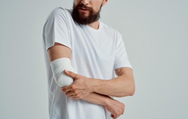 Homem com braço ferido enfaixando medicamento para paciente.