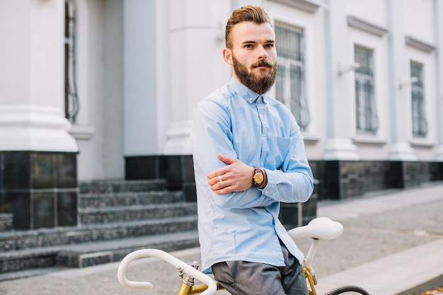 Homem com braços cruzados apoiado em bicicleta