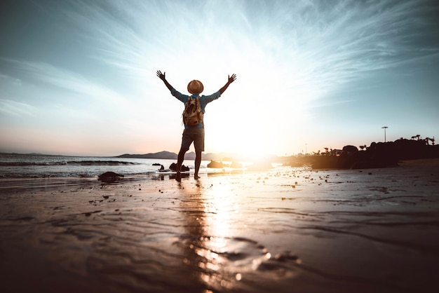 Homem com braços erguidos na praia ao pôr do sol