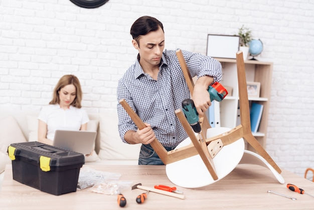 Homem com broca nas mãos que repara a cadeira na sala.