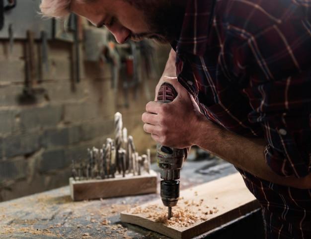 Homem com broca trabalhando com madeira