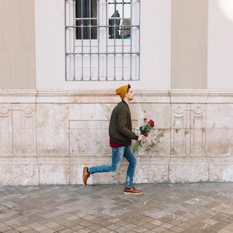 Homem com buquê correndo na rua