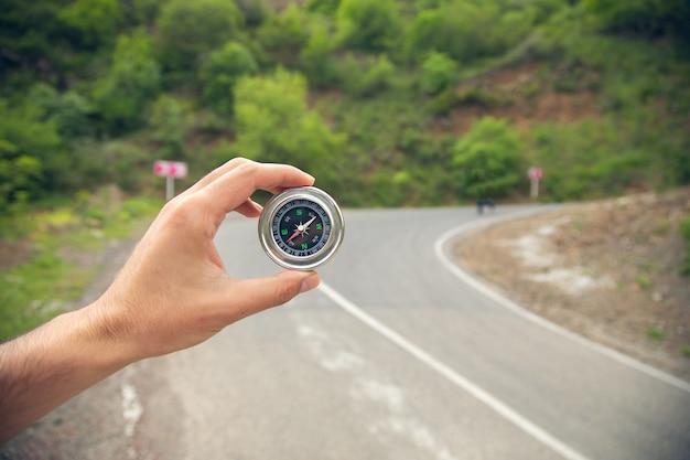 Homem com bússola em estrada de asfalto