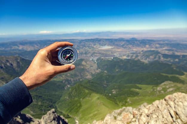 Homem com bússola no fundo da montanha