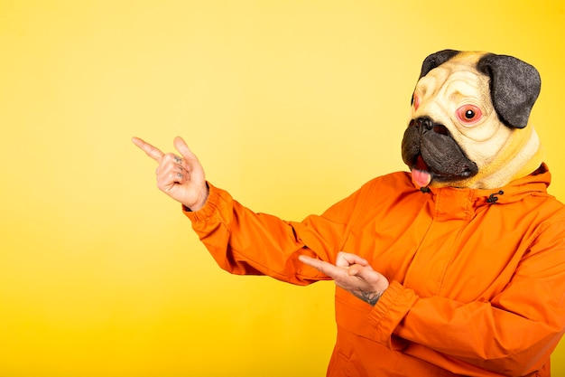 Homem com cabeça de cachorro, apontando para o lado com as mãos, com espaço para texto.