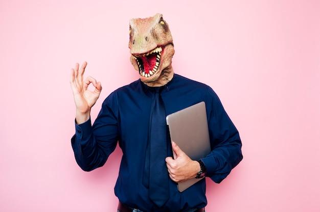 Homem com cabeça de dinossauro eufórico e dedos com o símbolo ok