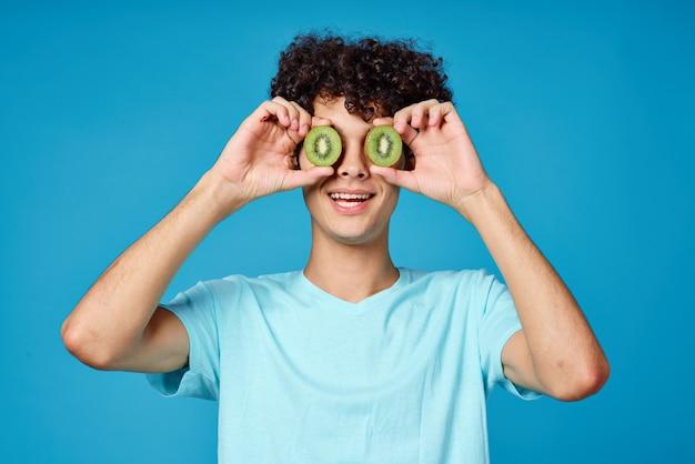 Homem com cabelo cacheado kiwi perto do rosto azul plano de fundo vista recortada