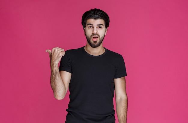 Homem com cabelo comprido e barba fazendo sinal de mão polegar para cima.