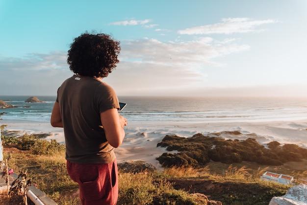 Homem com cabelo encaracolado olhando o mar rodeado de pedras e vegetação sob o sol