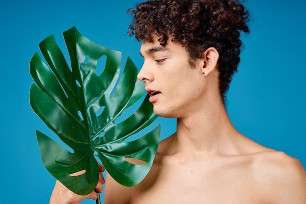 Homem com cabelo encaracolado, ombros nus, folhas verdes ecologia