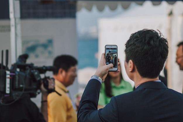 Homem com cabelo escuro, tirando foto de pessoas no smartphone