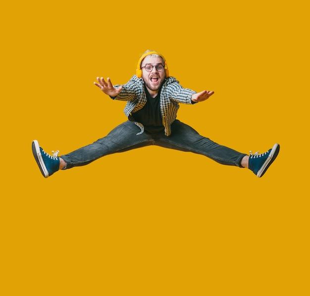 Homem com cabelo loiro e barba pulando na parede amarela de um estúdio enquanto ouve música com fones de ouvido