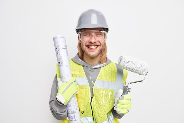 Homem com cabelo ruivo segura planta de papel e rolo de pintura, vestido com capacete de proteção, uniforme de óculos transparentes isolado no branco