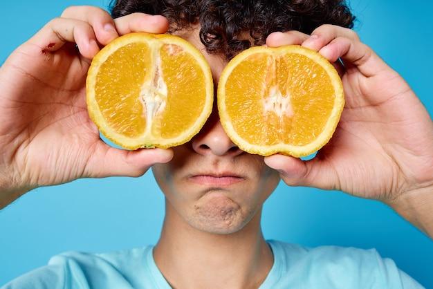 Homem com cabelos cacheados laranjas segurando fundo azul do estúdio de frutas