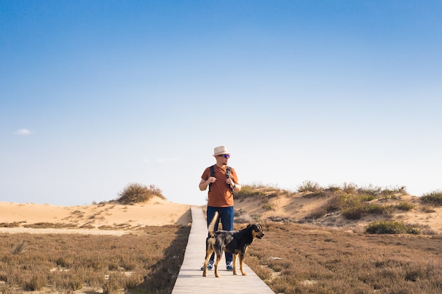 Homem com cachorro andando no caminho de madeira na praia e olhando para a distância do oceano.