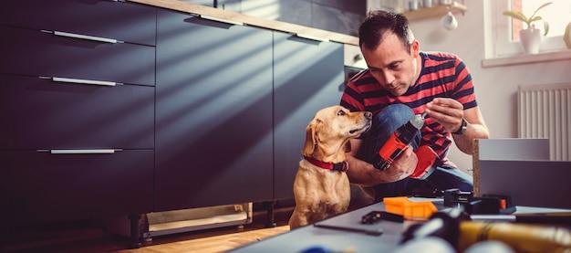 Homem com cachorro, construção de armários de cozinha