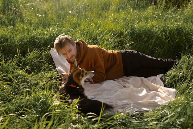 Homem com cachorro no cobertor, ao ar livre, foto completa