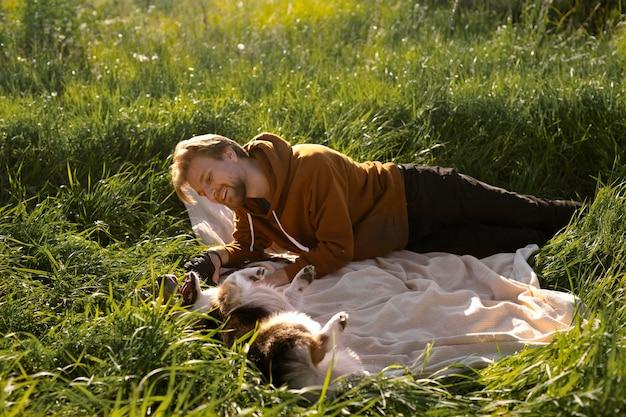 Homem com cachorro no cobertor, tiro completo