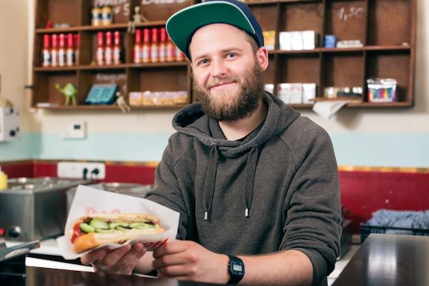 Homem com cachorro-quente na lanchonete de fast-food