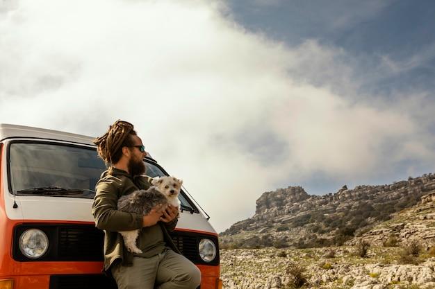 Homem com cachorro sentado ao lado do carro