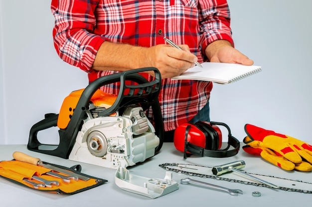 Homem com caderno diário, uma caneta na oficina. reparação de motosserras, ferramentas movidas a gasolina.