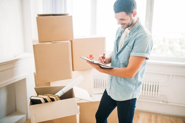 Homem com caderno entre caixas, inauguração de casa