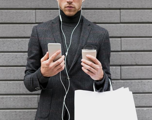 Homem com café e smartphone nas mãos