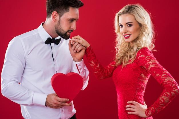 Homem com caixa em formato de coração segurando a mão de uma mulher
