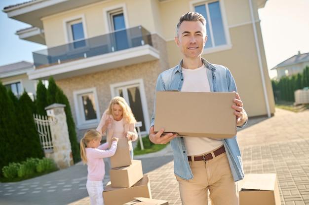 Homem com caixa, esposa e filha atrás