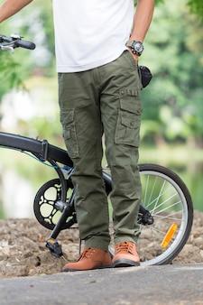Homem com calças cargo andando de bicicleta no jardim
