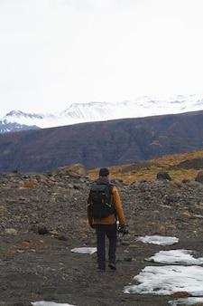Homem com câmera caminhando cercado por montanhas rochosas cobertas de neve na islândia