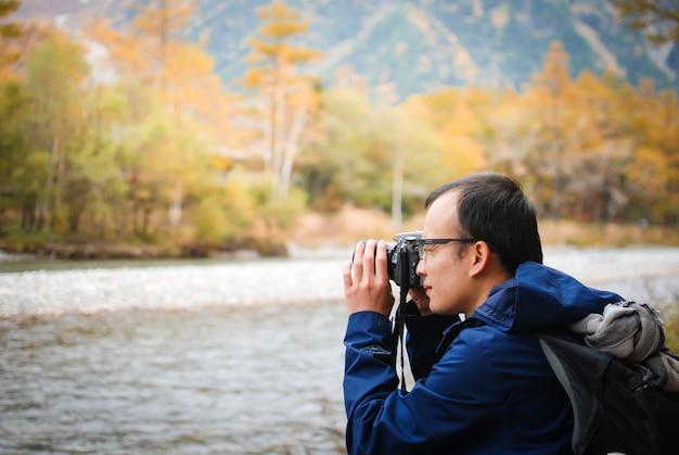 Homem com câmera e tirar fotos, sente-se perto do rio vento natural com floresta de outono