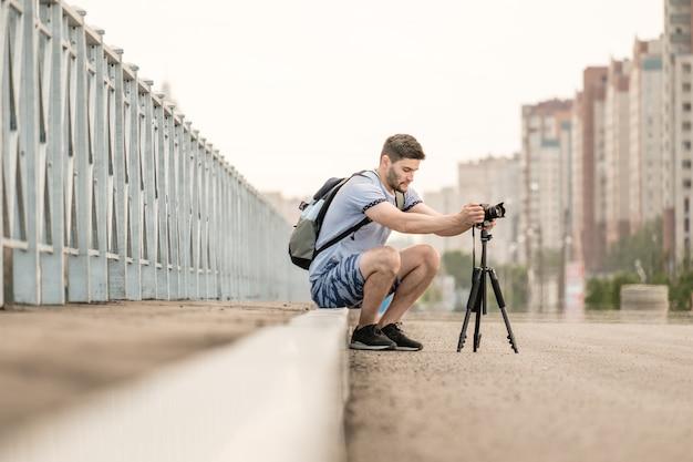 Homem com câmera fotográfica no tripé tirando fotos timelapse na cidade