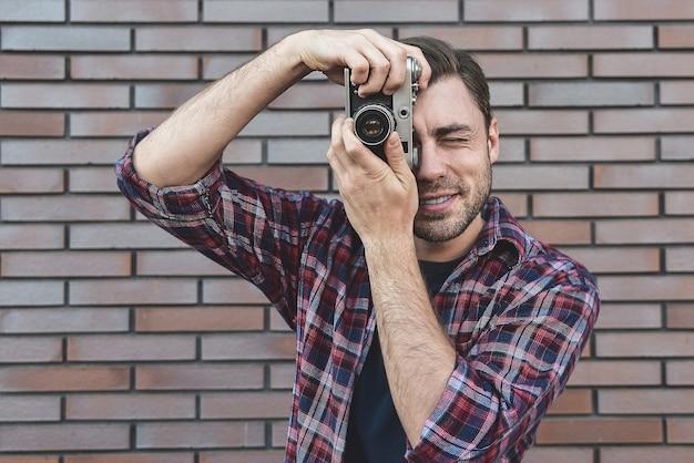 Homem com câmera fotográfica retrô fashion travel lifestyle ao ar livre em pé contra o fundo da parede de tijolo.