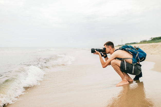Homem com câmera fotográfica tirando foto do mar. fotógrafo de homem localização na praia e tirar foto da natureza.
