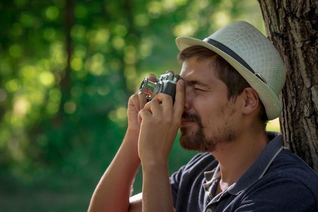 Homem com câmera vintage na floresta