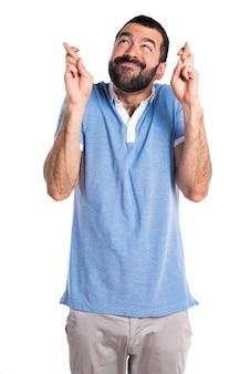 Homem com camisa azul com os dedos cruzados