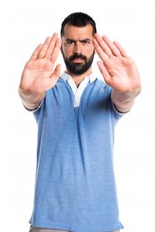 Homem com camisa azul fazendo sinal de parada