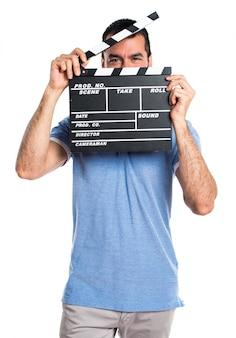 Homem com camisa azul segurando um clapperboard