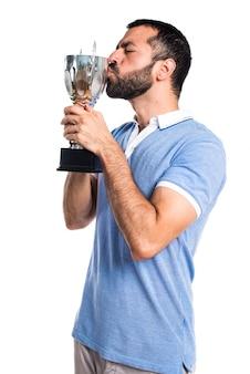 Homem com camisa azul segurando um troféu