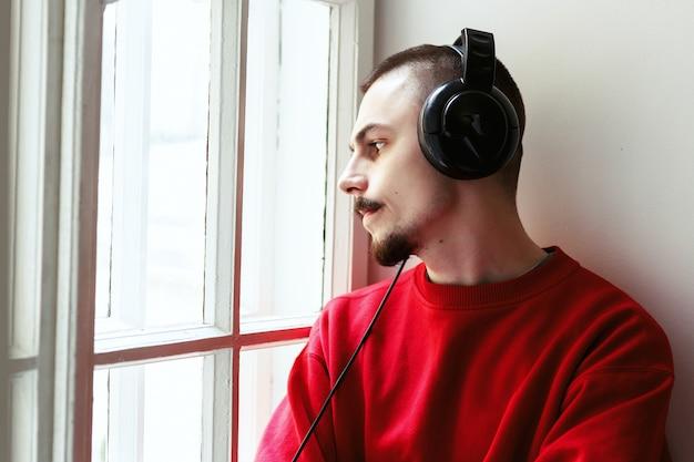 Homem com camisa de corpo vermelho escuta a música sentada no peitoril da janela