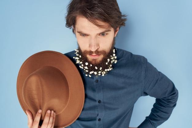 Homem com camisa de flores com emoções de chapéu de barba