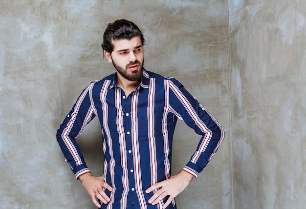 Homem com camisa listrada parece confuso e pensativo.